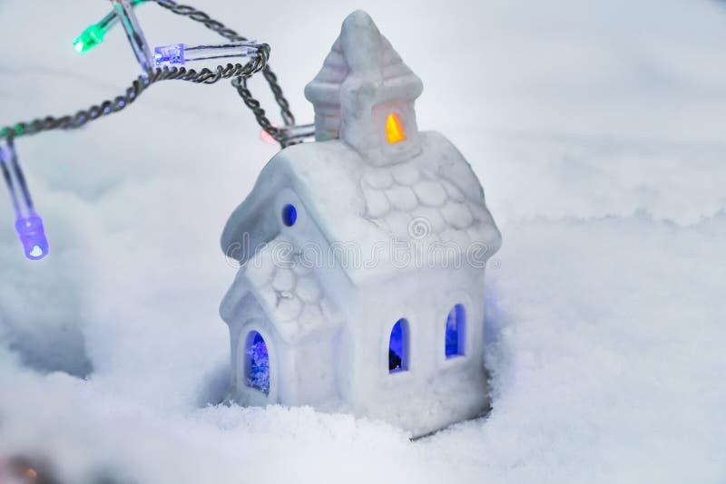 Ett härligt sagolikt litet vitt hus med gula och blåa ljus i fönstren och girlanderna av att bränna färgrika lampor på a arkivbilder