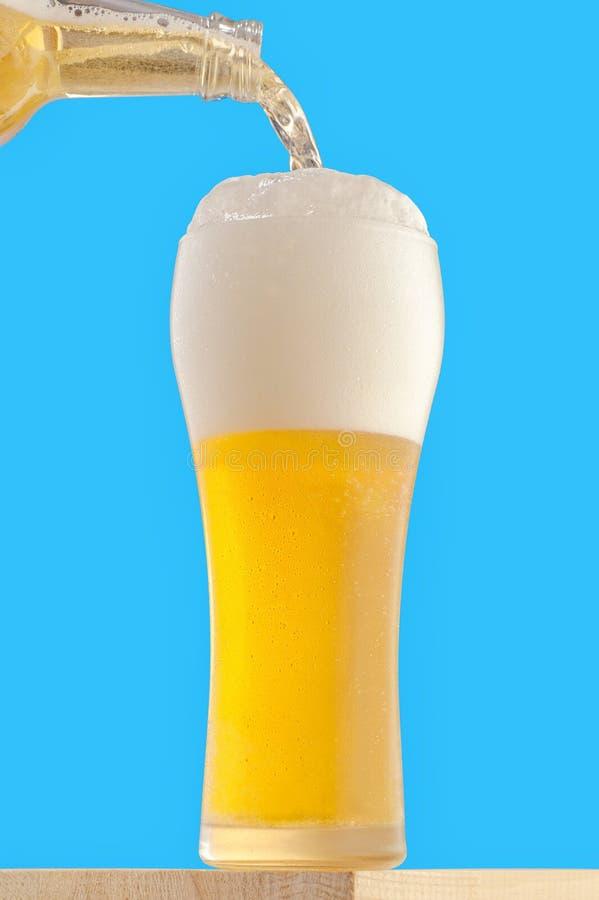 Ett högväxt exponeringsglas med ett ljust kylt öl royaltyfri bild