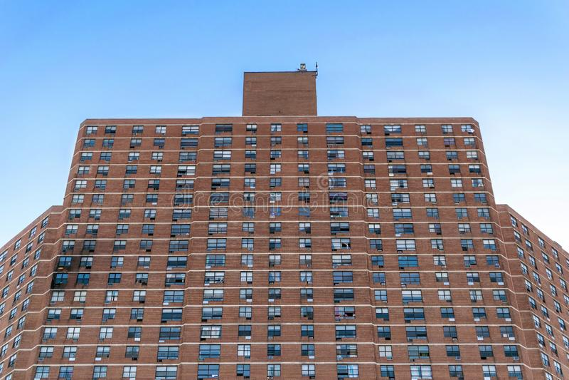 Ett högväxt hyreshuskomplex i Harlem, med synlig brandskada på vänstra sidan, New York City, NY, USA royaltyfri fotografi