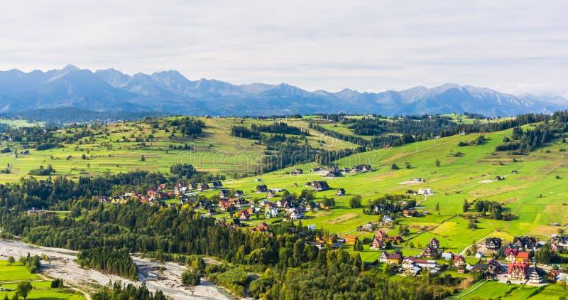 Ett höstligt landskap Fördelad utveckling i den turist- semesterorten Bialka Tatrzanska på floden, ängar, skogar och Tatren arkivbilder