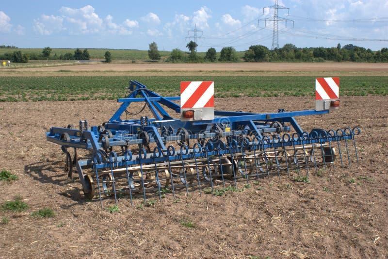 Ett harv som kan användas till mycket för aerating fält, fördelande sugrör och att odla skäggstubb och slåss ogräs arkivbilder