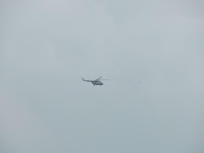 Ett helikopterflyg mot bakgrunden av grå himmel royaltyfria bilder