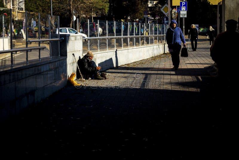 Ett hemlöst ogiltigt frågar för pengar på gatan, och hans katt gör ett företag i Burgas/Bulgaria/12 06 2018/ fotografering för bildbyråer