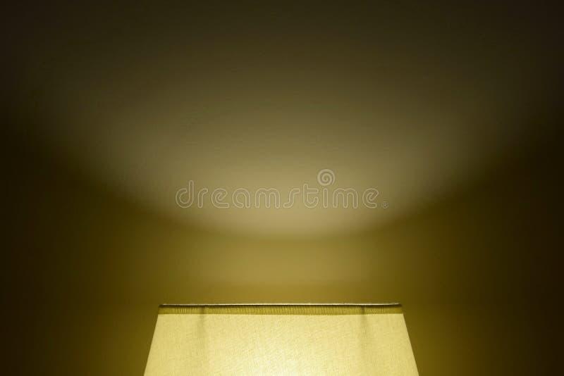 Ett hemtrevligt mjukt ljus från en lampskugga på väggen i ett mörkt rum Panelljus underifr?n arkivbilder