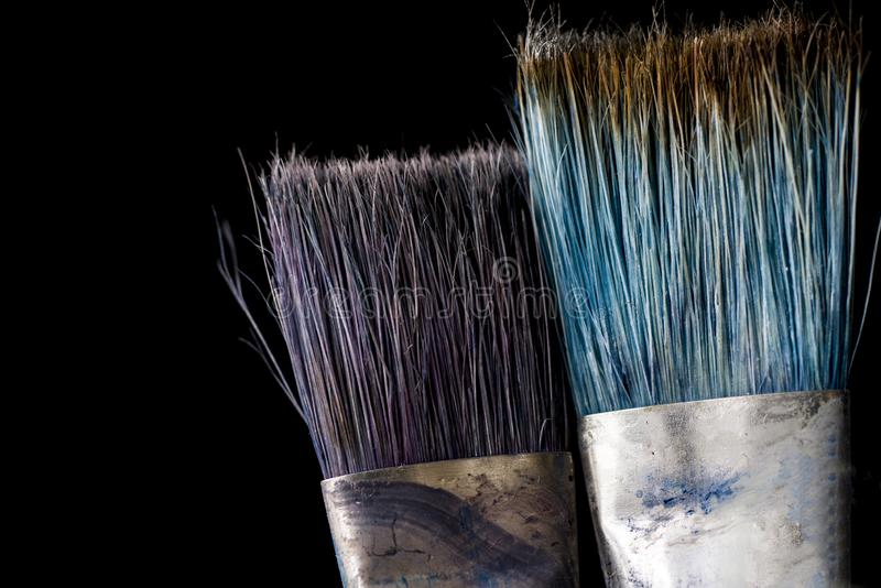 Ett hjälpmedel för konstnärens arbete Två borstar i målarfärgnärbild på en svart bakgrund royaltyfri fotografi