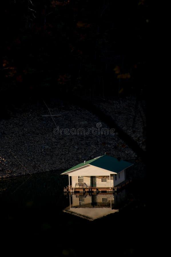 Ett hus för litet fartyg som tänds av ljust solljus, svävar i en behållarsjö fotografering för bildbyråer