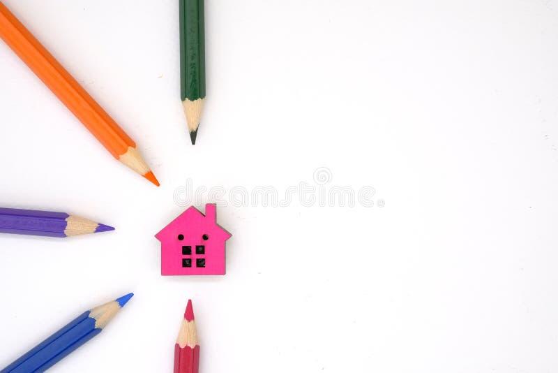 Ett hus och färgade blyertspennor arkivbild