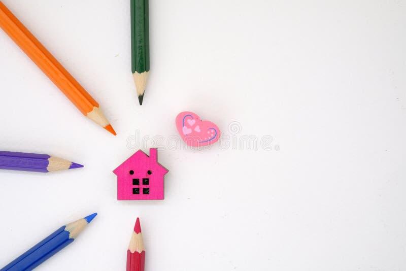 Ett hus och färgade blyertspennor royaltyfria foton