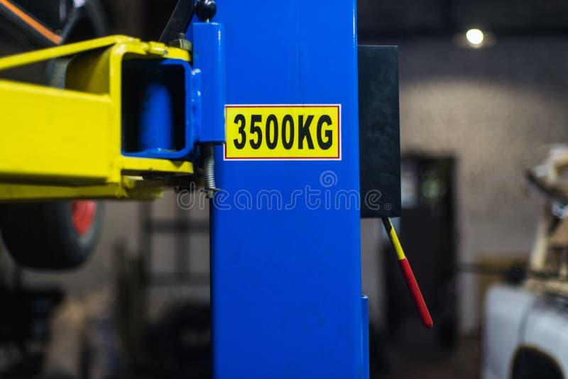 Ett ID-Märke på den blåa bilelevatorstolpen arkivfoton