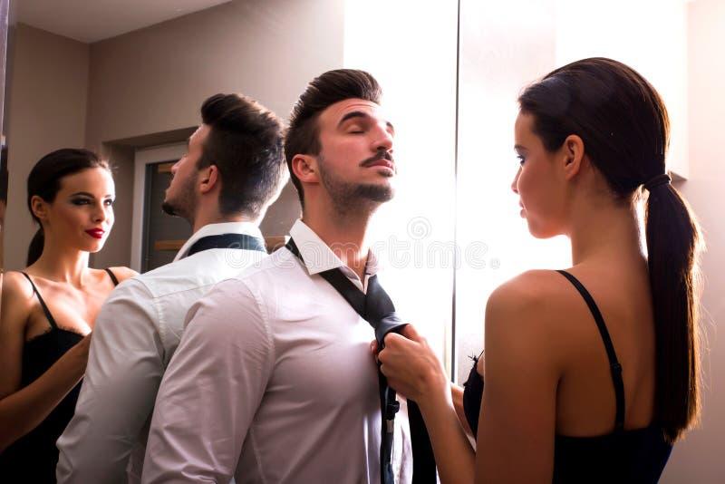 Ett iklätt ungt par få det ändrande rummet royaltyfria bilder