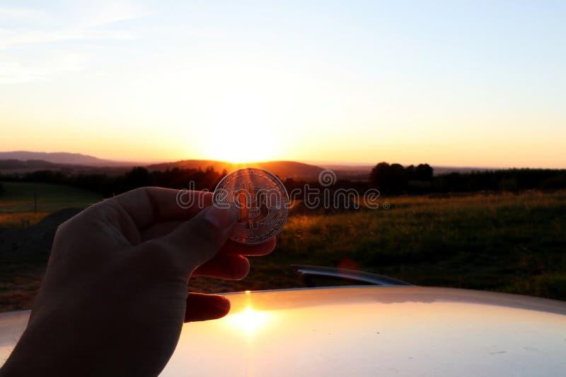 Ett innehav för investeringrådgivare i liten guld- bitcoin för hand och i den härliga solnedgången för bakgrund fotografering för bildbyråer