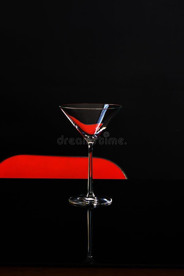 Ett isolerat exponeringsglas för martini på mörk och röd bakgrund coctail royaltyfria bilder
