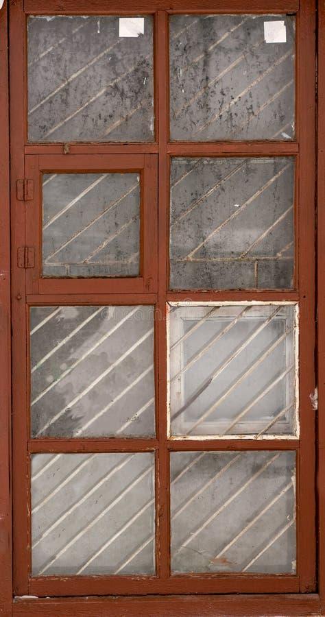 Ett isolerat gammalmodigt fönster av ett gammalt hus med djupfryst exponeringsglas och träramen på viten arkivfoton