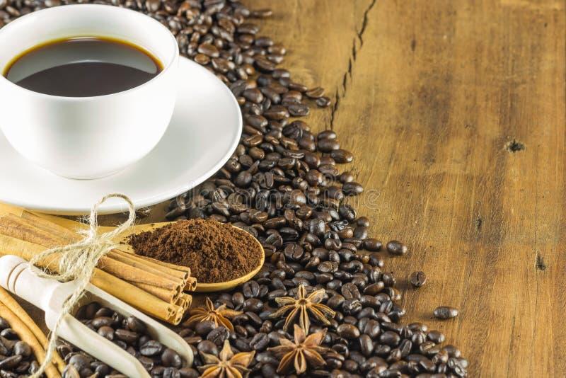 Ett kaffe på koppen med kaffebönor och kanelbruna pinnar på trä arkivfoton