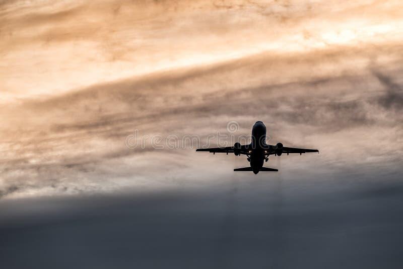 Ett kommersiellt flygplan under start från flygplatsen Kontur som flyger över himmel på solnedgång- eller soluppgångbakgrund, arkivbilder