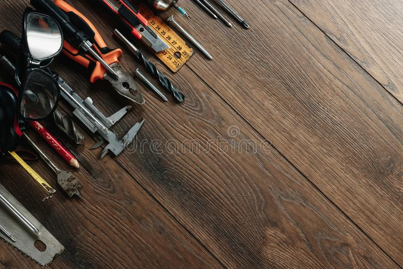Ett konstruktionshjälpmedel på en brun träbakgrund ovanför sikt Bildbakgrund, screensaver Begreppet av konstruktion, r royaltyfri fotografi