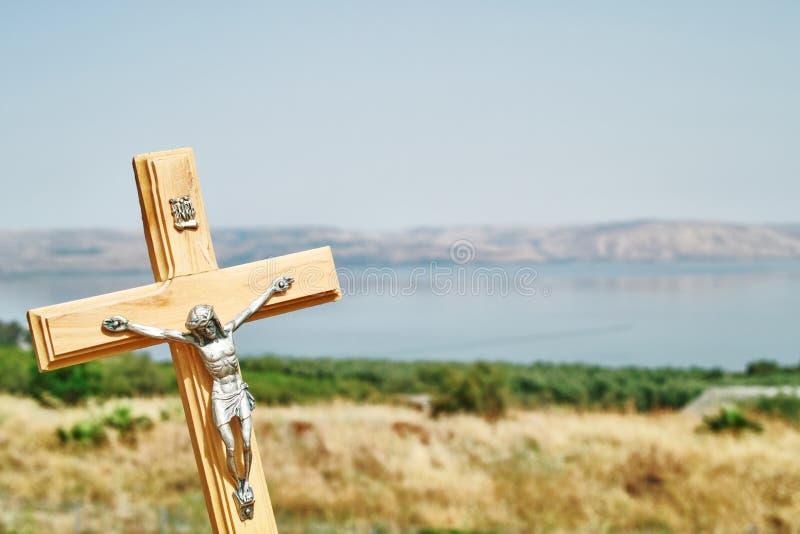 Ett kors med bakgrund av havet av Galilee och Capernaum som beskådas från kyrkan av saligheterna, Israel royaltyfri fotografi