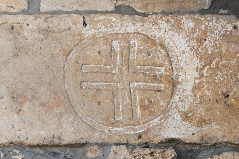 Ett kors sned på en stenvägg på fasaden av en kyrka av Christian Maronites i den övergav byn Kafr Birim i eller royaltyfri bild