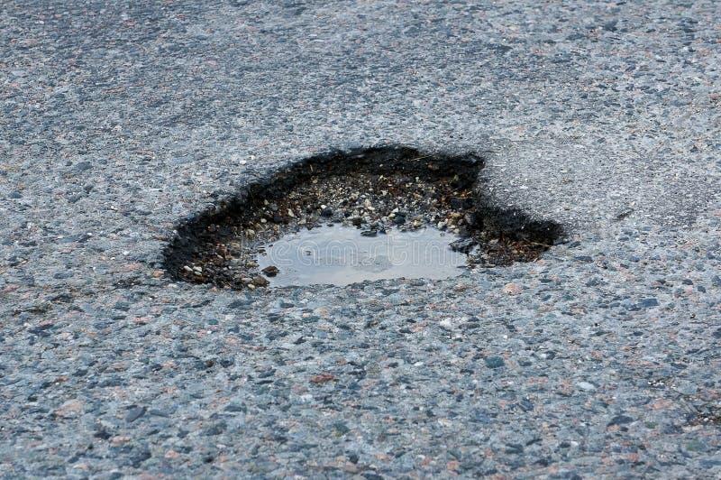 Ett krukahål i asfalten royaltyfri bild