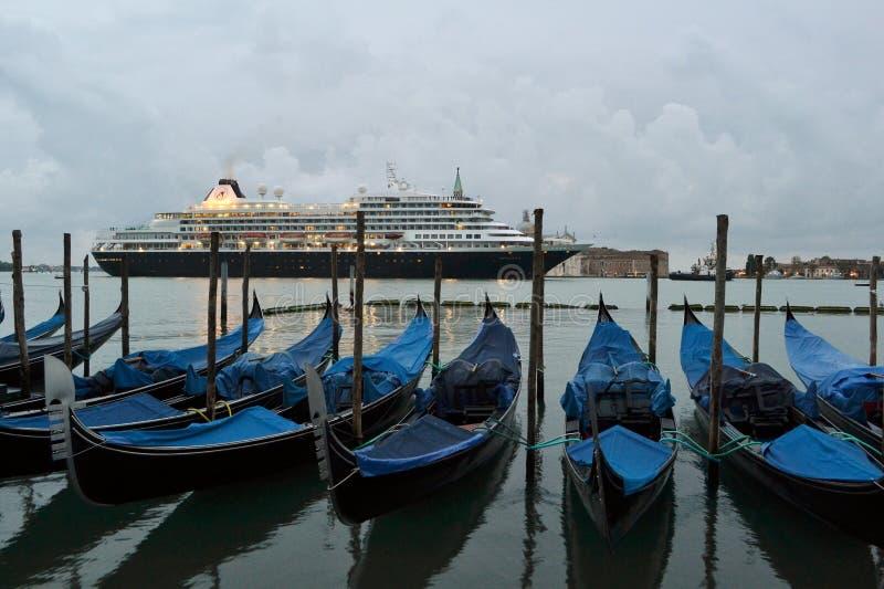 Ett kryssningskepp som korsar morgonen för vår för Venedig lagun den tidiga på gryning och blåa gondoler som ankras på sjösidan royaltyfri fotografi