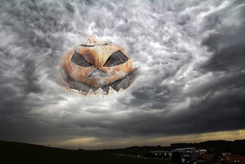 Ett kusligt halloween pumpahuvud i himlen mellan åskmoln ser en stad arkivbilder