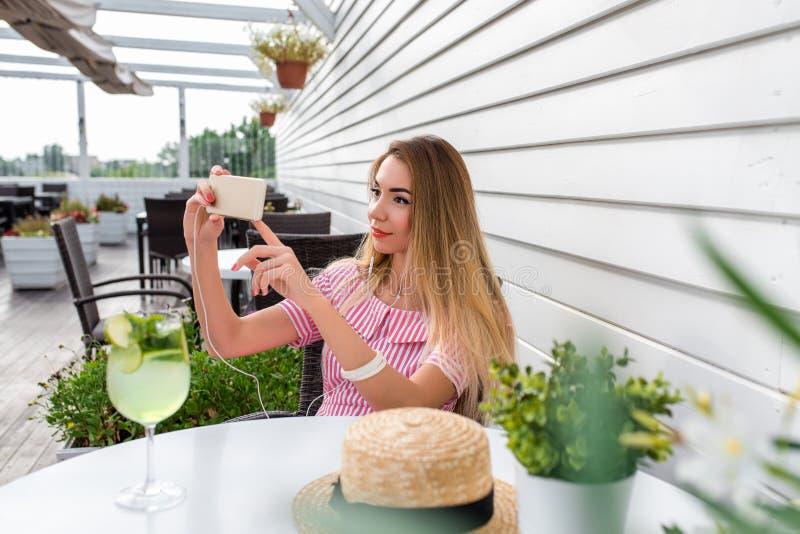 Ett kvinnakafé och att ha sommarlunchfrukosten, fotografier ringer, online-internetappellen Det sociala nätverket för applikation arkivbilder