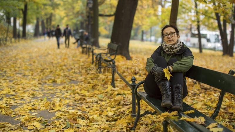 Ett kvinnasammanträde på en bänk i höst parkerar Gå arkivbilder