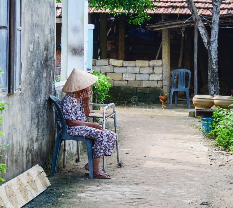 Ett kvinnasammanträde på gatan i Hoi An, Vietnam royaltyfri foto