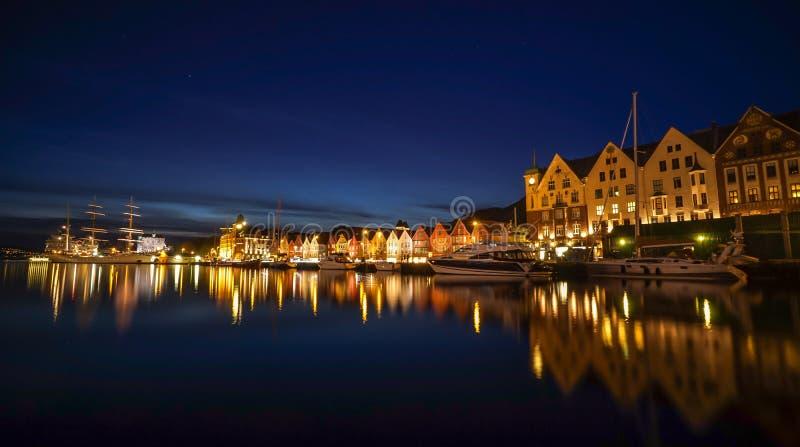 Ett långt exponeringsfotografi för natt av Bergen på hamnen med härlig vattenreflexion royaltyfri foto