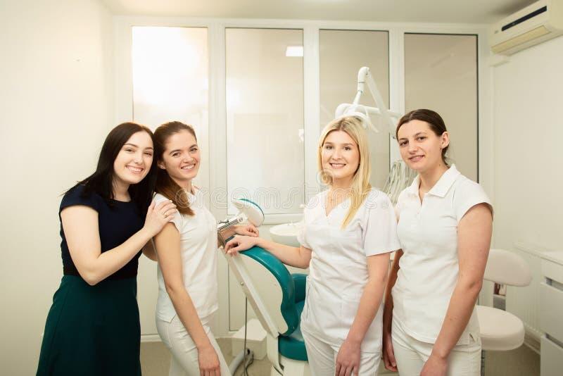 Ett lag av professionell i en tand- klinik som poserar nära utrustningen royaltyfri bild