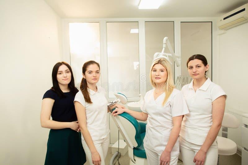 Ett lag av professionell i en tand- klinik som poserar n?ra utrustningen arkivbilder