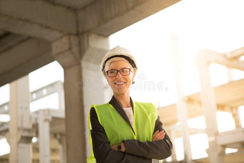 Ett lag av unga kvinnor och två blickar för unga män på byggnadsplan royaltyfria bilder