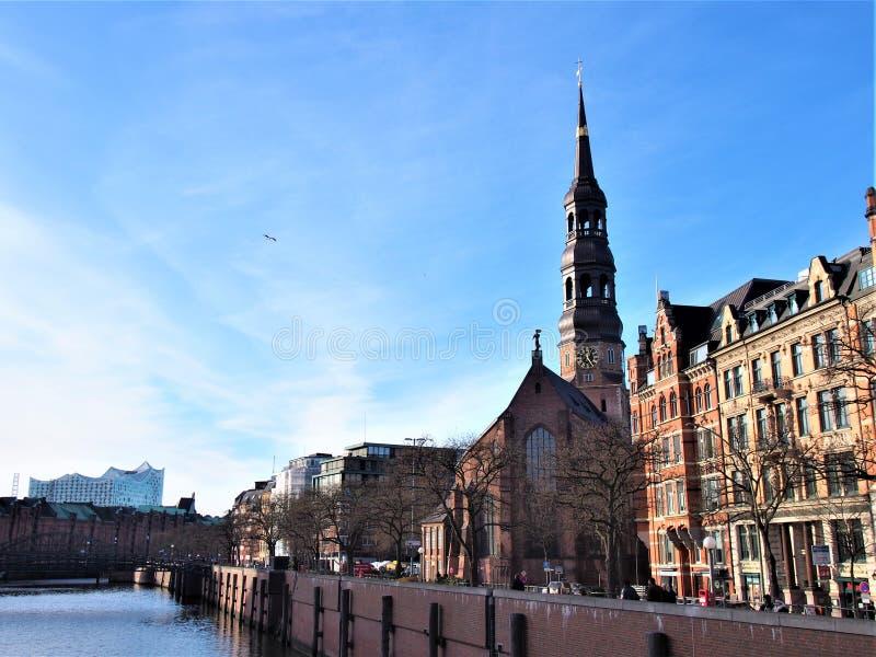 Ett landskap av Hamburg St Katharinen, kanal och Elbphilharmonie arkivbilder