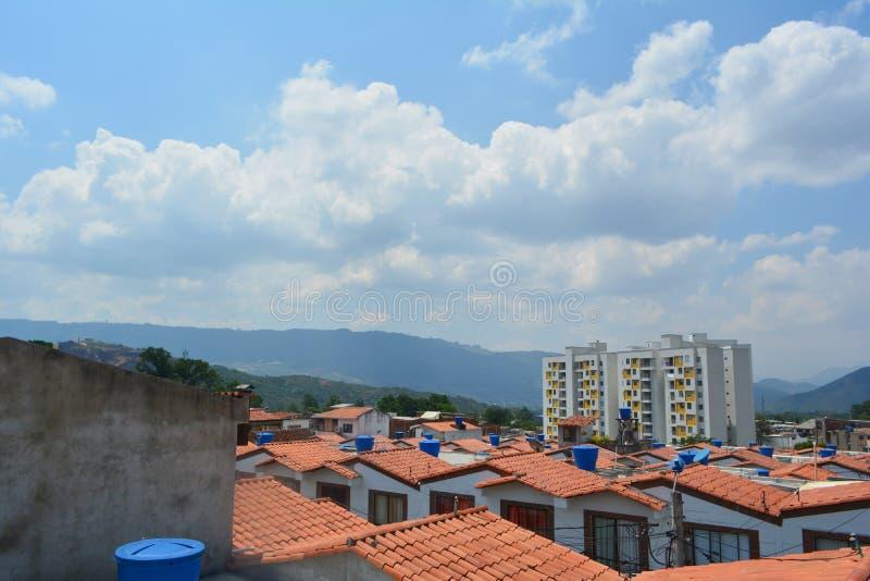Ett landskap av något inhyser sett från taket och en betongvägg med en blå himmel i bakgrunden arkivfoto