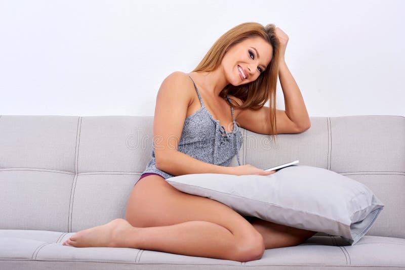 Ett le kvinnasammanträde på en soffa och använda hennes smartphone arkivbild