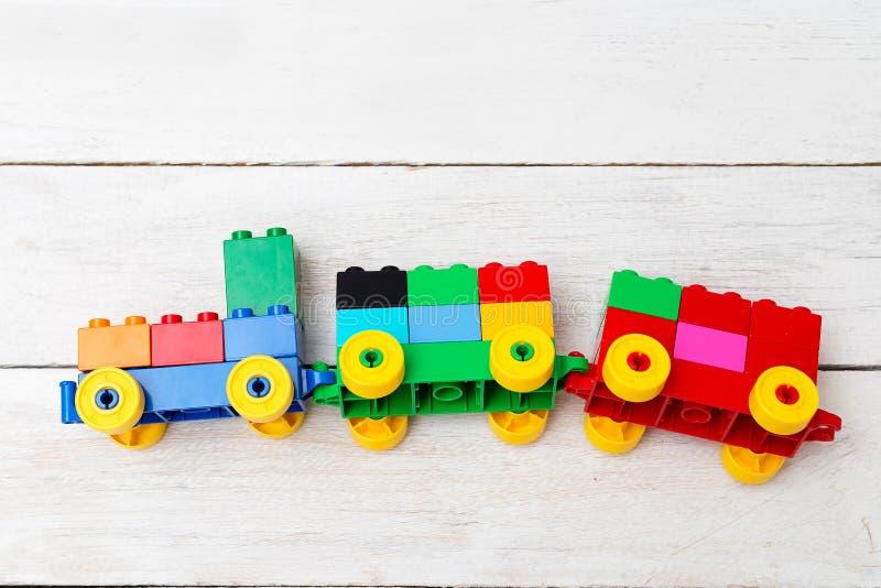 Ett leksakdrev av kuber av legoen på en träbakgrund bilda royaltyfria foton