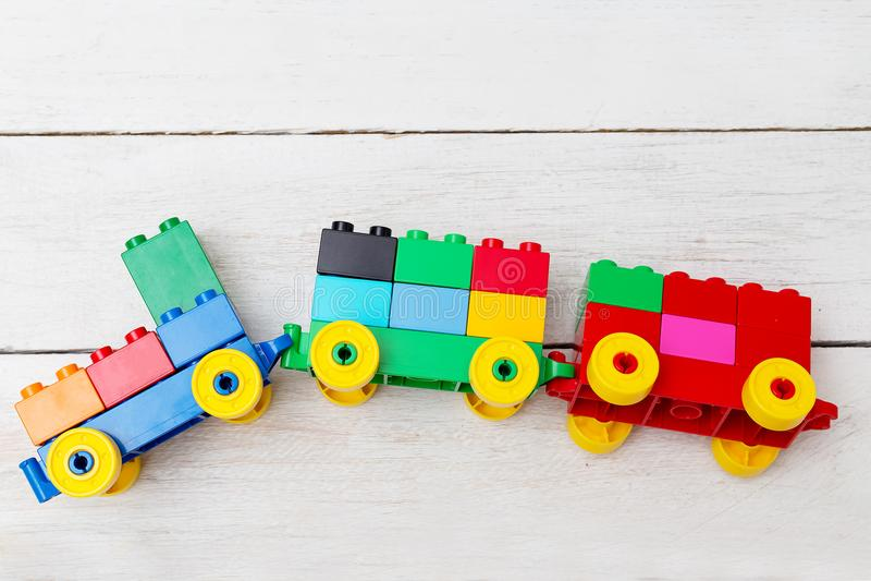 Ett leksakdrev av kuber av legoen på en träbakgrund Lekmanna- lägenhet arkivbilder