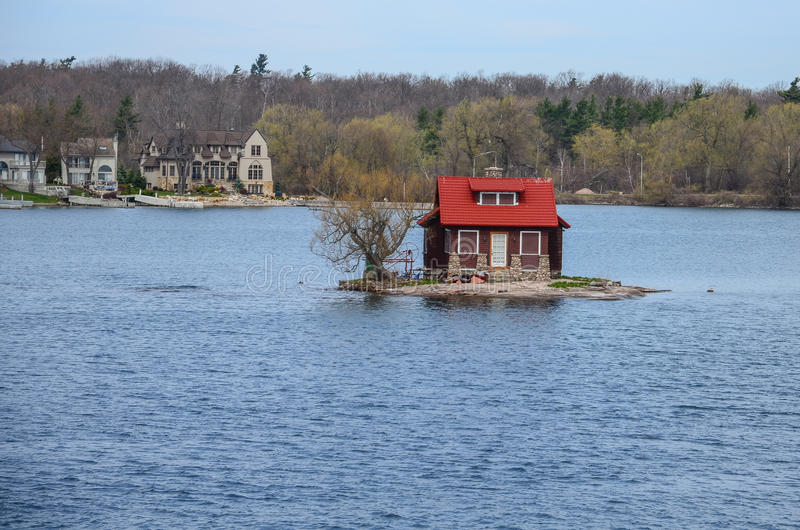 Ett litet ö och strandhus på St Lawrence River royaltyfria bilder