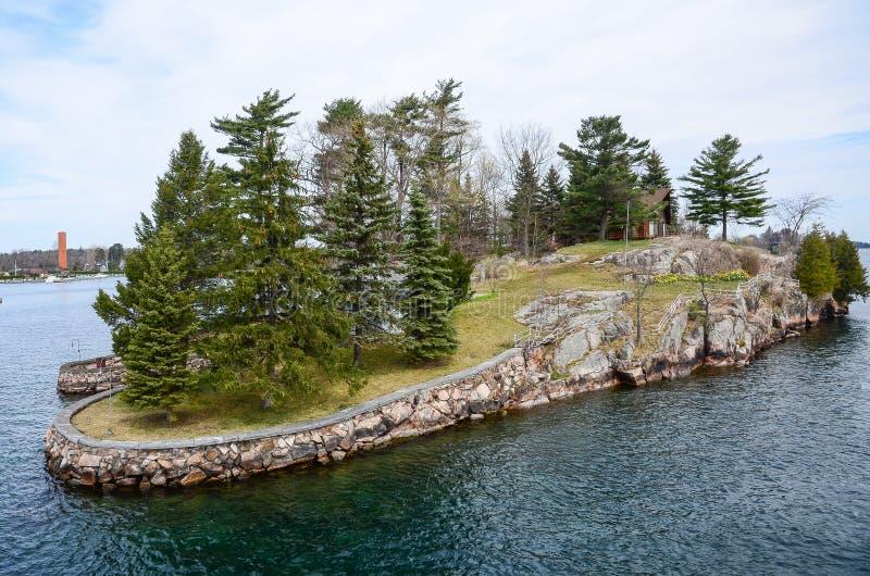 Ett litet ö och strandhus på St Lawrence River royaltyfria foton