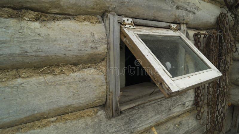 Ett litet öppet fönster in i huset som göras av timmer- och lerasläp arkivbilder