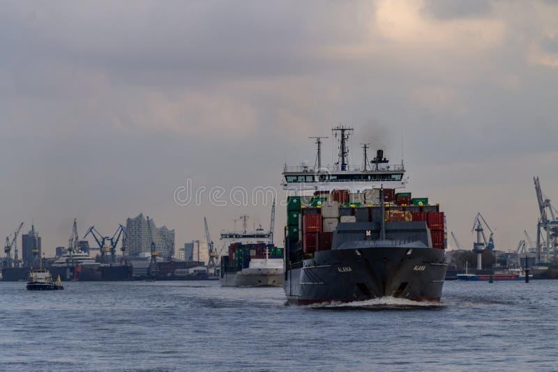 Ett litet behållareskepp som att närma sig den Hamburg hamnen arkivfoto
