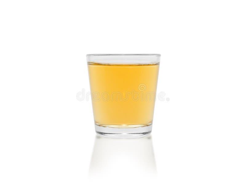 Ett litet belopp av whisky i en glass bägare som isoleras på en vit bakgrund royaltyfri bild