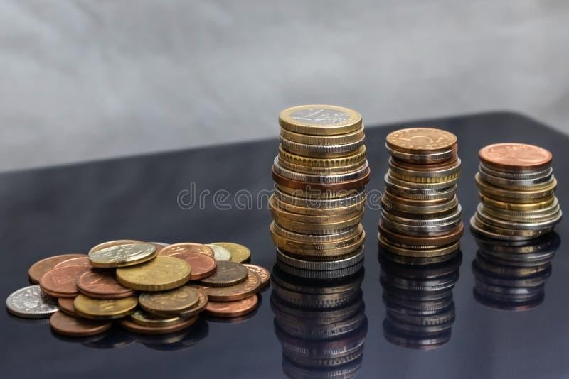 Ett litet berg av mynt från olika länder och tre torn av mynt arkivbilder