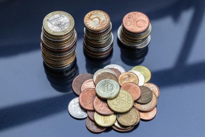 Ett litet berg av mynt från olika länder och tre torn av mynt royaltyfri foto