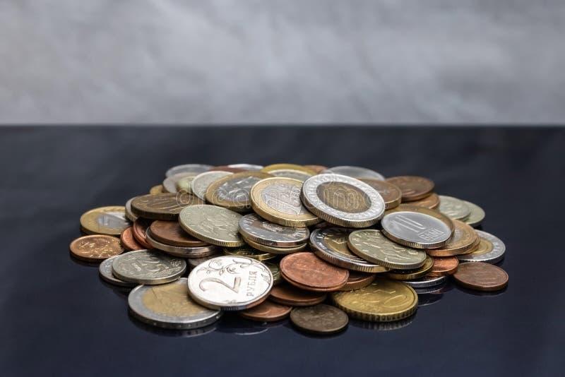 Ett litet berg av mynt från olika länder royaltyfri foto