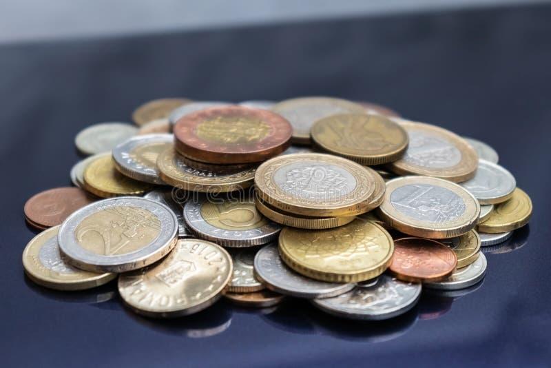 Ett litet berg av mynt från olika länder royaltyfri fotografi