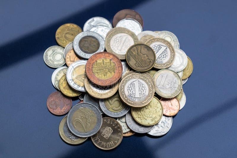 Ett litet berg av mynt från olika länder på en blå bakgrund royaltyfria bilder
