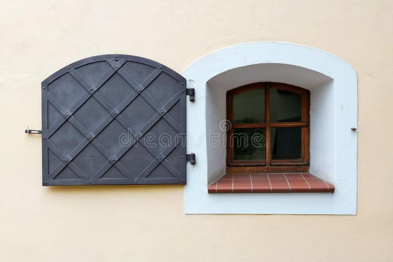Ett litet fönster i den gula väggen av ett medeltida hus är skyddar royaltyfri foto