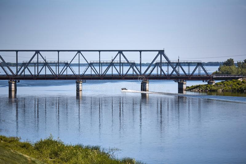Ett litet fartyg seglar längs floden i en solig dag för sommar under en järnvägsbro royaltyfria foton