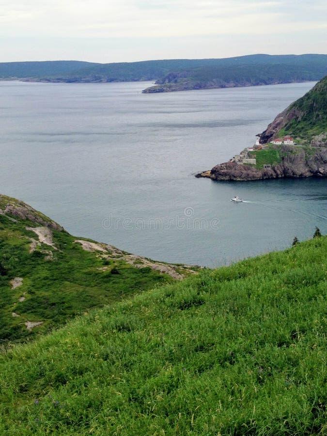 Ett litet fartyg som lämnar hamnen för St John ` s på en blåsig dag för sommar` s arkivbild